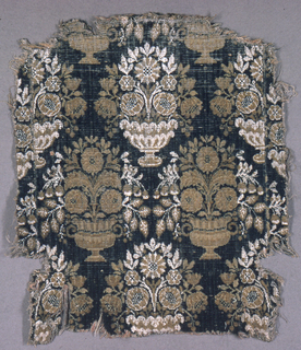 Large repeat of symmetrical bouquet in urns; rose and tan wool, white linen, on dark blue-green wool ground. Broad warp-surfaced plain cloth selvages.