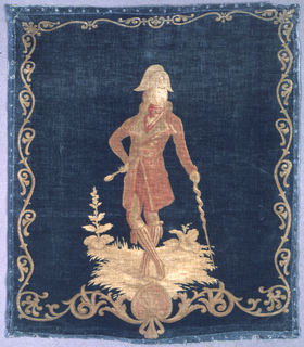 Square cushion cover of printed cotton velvet with a standing figure of a man in fashionable dress with striped hose and a bicorn hat leaning on a spiral walking stick. In rosy reds and tans on a blue-green ground, with a narrow scrolling acanthus border.