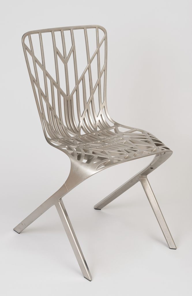 Cantilivered openwork chair, the back with open radiating and vertical lines that merge into a sold seat supported by two raking legs that split into a Y.