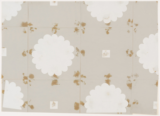 Large flat white flower motif alternating with white squares and gray paper squares. The inspiration for this design was the sixteen petaled chrysanthemum, the emblem of the mikado, or emperor of Japan. The square at the center of each flower may refer to the tsuba, or ornamental sword guard.