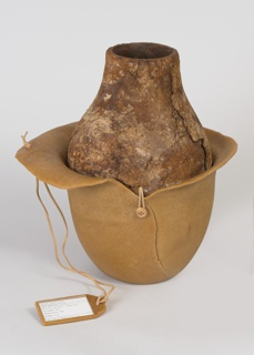 Ovoid form with slightly tapered neck and circular mouth. Body consists of two materials: upper made from two halves of bois durci (sycamore wood and egg albumen) and lower made from two petals of dewaxed shellac. Upper and lower pieces joined in two spots with leather cord and button detail. Leather cord attaches a printed paper tag encased in dewaxed shellac and glass to larger petal, which reads: 