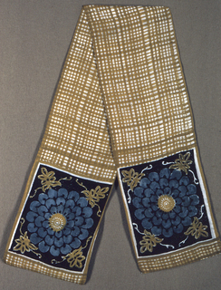 Short, narrow scarf of dark gold, black and turquoise blue. Central section has a small-scale plaid in dark gold. Scarf ends show a large, open stylized flower head in turquoise blue with corner decoration in dark gold on a black ground.