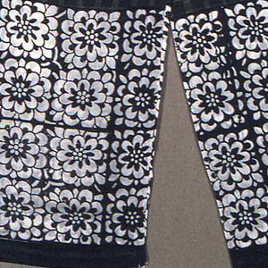 Black and gray scarf with a small-scale plaid design in the center. Scarf ends show four rows of four conventionalized flower heads.