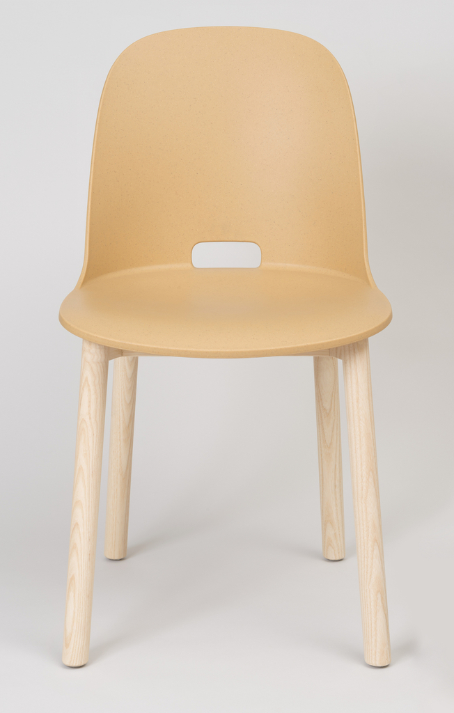 Tall side chair with rounded back and flat seat on four straight, thin cylindrical legs. An elliptical hole in the back of the seat serves as a handle.