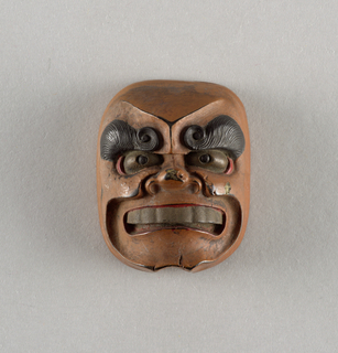 Mask with heavy eyebrows spiraled at inner corners and wide grinning mouth. Inside of mouth and corners of eyes are lacquered red, the eyebrows and pupils black, and the eyeballs and teeth gold. The inside of the mask is lacquered brown.