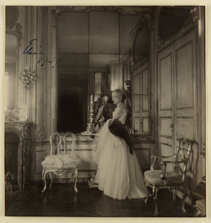 Square frame (a) of mirror glass with simple narrow bamboo molding around outer and inner edges; frame contains signed sepia-toned photograph (b) of Elsie De Wolfe dressed in evening gown, standing in mirrored paneled interior.