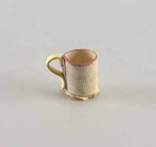 Pink mug with yellow base and handle.
