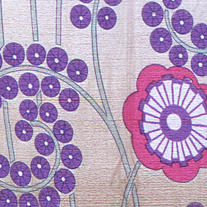 Stylized flowers printed in purple and bright pink on a ground that shades from brown to light brown.