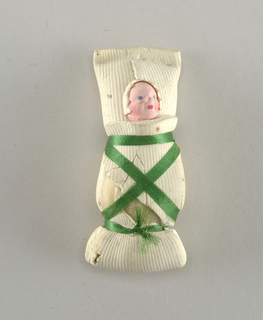 Swaddled baby, tied with green ribbon.