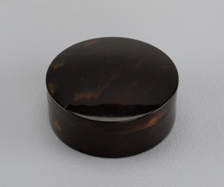 Circular tortoiseshell box with lid.
