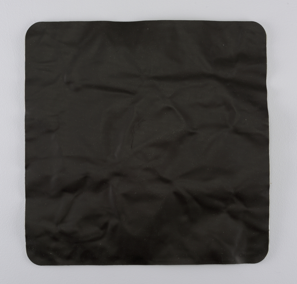 Flat square composed of two mat black rubber sheets with a flexible aluminum sheet sandwiched in between.