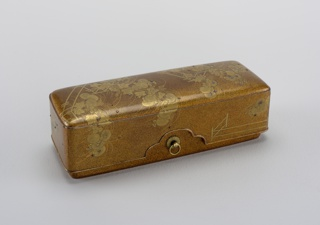 Rectangular box with curved corners and an over-lapping cover; the cover is deep with a three-lobed cut in the center of each long side; these frame two brass rings, threaded on chrysanthemum mounts affixed to the box; the mounts are screwed to the box sides and capped with raised disks inside the box; the cover has a slightly convex upper surface. Both box and cover are painted with a gold 'nashiji', the rims of the two pieces are painted in matte 'fundame' gold. The cover and sides of the cover and box are decorated with diagonally bent fences against which sprays of chrysanthemum and grasses grow.