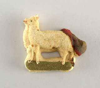 Lamb-like animal, standing on green grass, in relief.