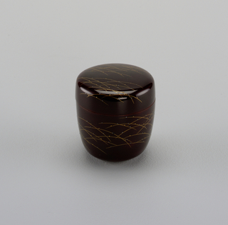 Cylindrical box, rounded at bottom and slightly flaring. Cover flat, with rounded edge. Brown lacquer with grass straws in gold and relief dots in gold and silver. Relief mark on bottom.