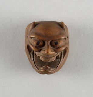 Mask of grinning demon, horned; the mouth is open and pierced through. The pupils are black.