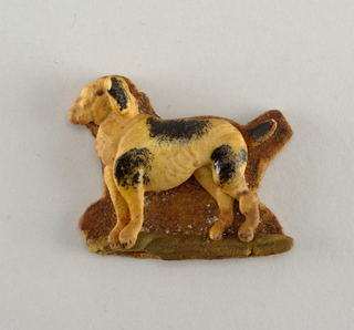 Dog-like animal with black spots, in relief on brown ground with strip of green.