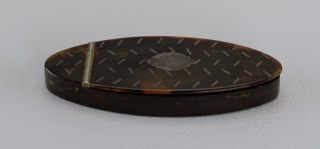 Small, thin, elliptical-shaped tortoiseshell box, top lid split by metal hinge towards one end, allowing box to open. Top detailed with pattern of short diagonal lines