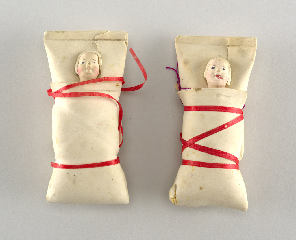Swaddled babies, tied with red ribbon.