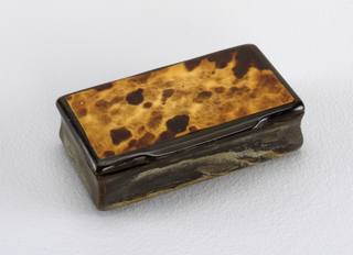 small rectangular box of bone, black with hinged lid and thin veneer of tortoise-shell on lid. Sides of box are curved from top to bottom (convex, concave, convex)