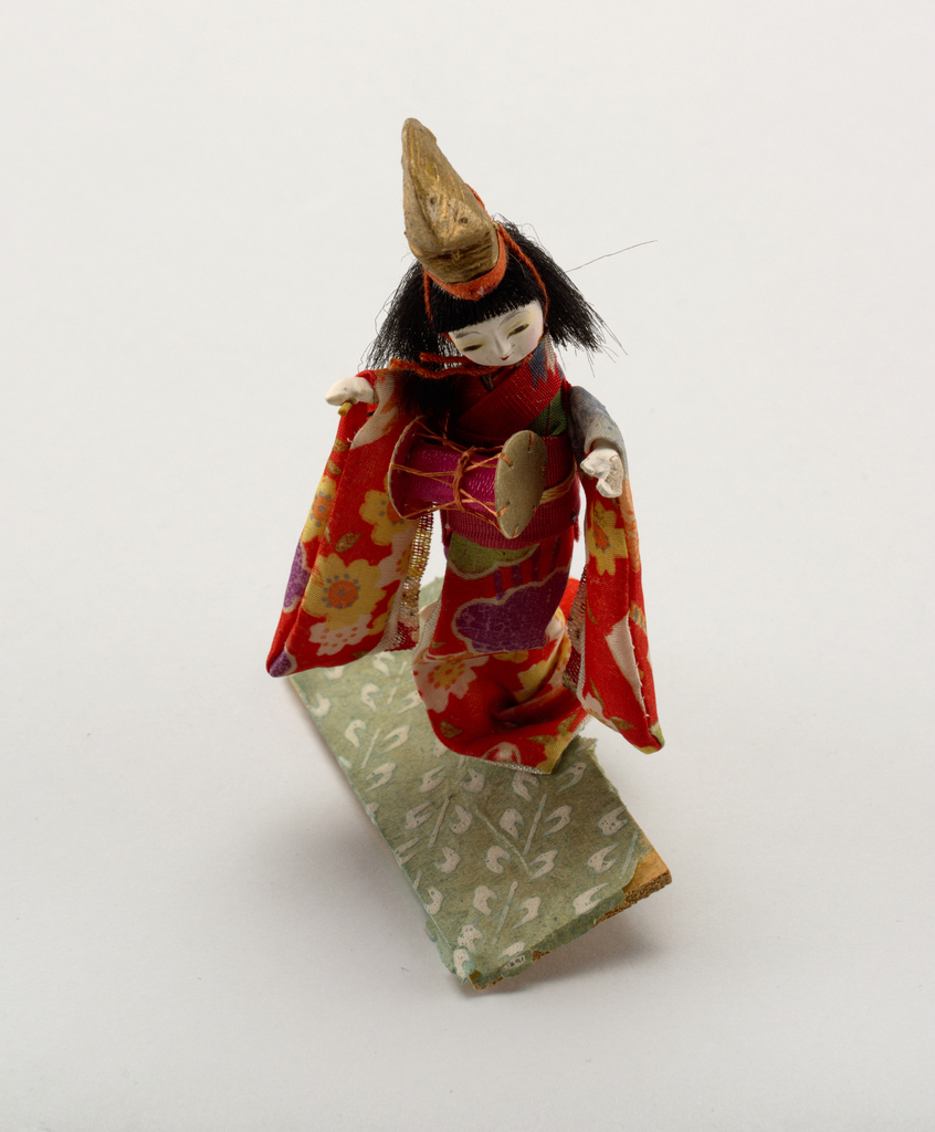 Figure of a dancing girl in native costume beating a drum.  Wood base of vitrine lined with green figured paper.  Glass bound in red tape.  Top held to base with tied pink silk tape.