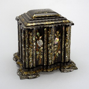 """Elaborately contoured square box with stepped, slightly domed, hinged lid with scalloped edges; stepped, scalloped base with four broad feet; the black lacquer ground with overall floral and foliate decoration of mother-of-pearl inlay, gilding and touches of paint; lid with scene of large church in landscape, """"Melrose Abbey"""" in small letters painted under scene; lid opens over compartmented top section; double doors in front open to reveal four drawers, the bottom one designed like a lap desk with hinged flap; drawer and compartment linings of silk, velvet, paper; ivory and mother-of-pearl tape measure container and emery container; small metal key."""