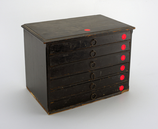 """Miniature chest of drawers, rectangular, with chamfered corners, molding around bottom, top. One wire ring pull at center of each velvet-lined drawer. Containing 150 plaster impressions of seals, the majority depicting classical figures, edges wrapped in paper edged in gold. Leather-covered """"catalogue""""."""