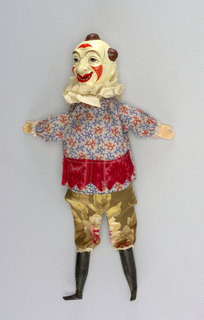 Brightly painted clown's head. White ruff at neck. Printed top with red skirt and flowered pants. Lace at knees and wrists. Black hose and shoes.