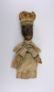 Carved head with small black beard, black moustache. Beige velvet cap with green bands. Natural cotton sleeves banded in green. Cotton twill cape, banded in green, a later addition. Carved wooden hands nailed onto the sleeves.