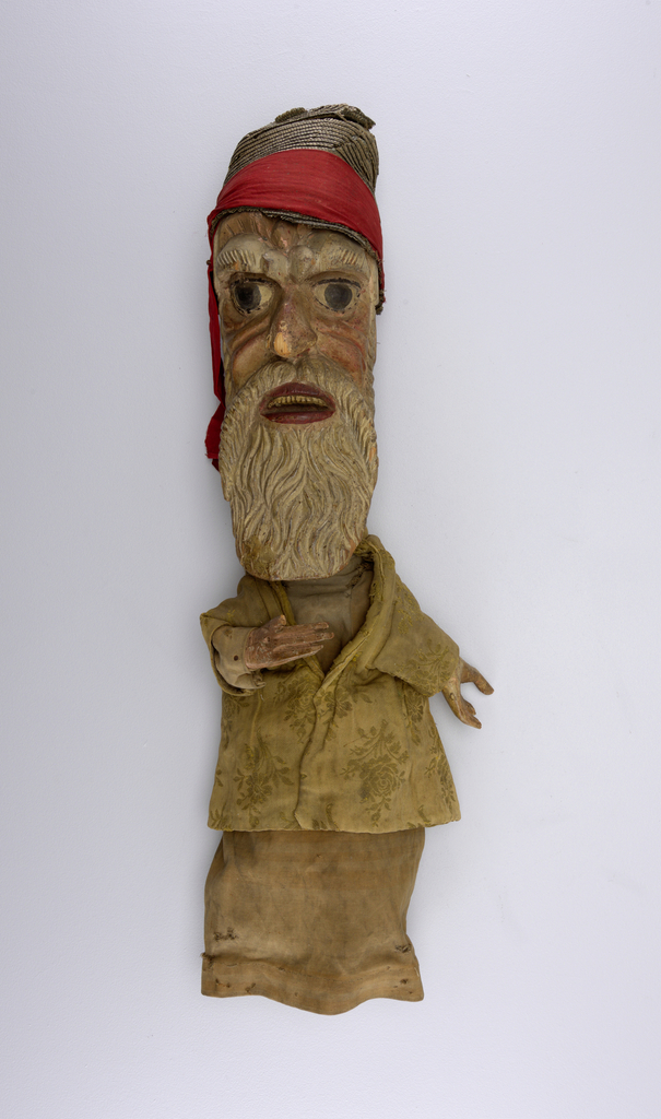 Head of an old man with busjy eyebrowns and wavy white beard. Yellow crocade coat. Pierced hands nailed onto sleeves. Conical straw hat.