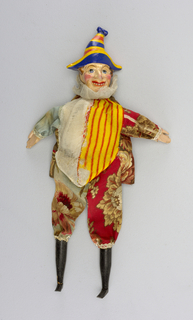 Brightly painted head in a tall striped bicorn hat. Black boots. Flowered suite with half white and half striped vest. Rosy cheeks and exposed teeth.