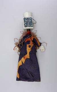 Square head with abstract painted face in blue, black and white. Sailor's hat. Purple robe with orange detail. Pipe cleaner at neck.