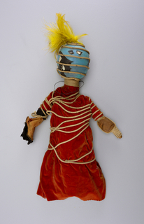 Round blue head with yellow feather. Red robe wrapped in twine.