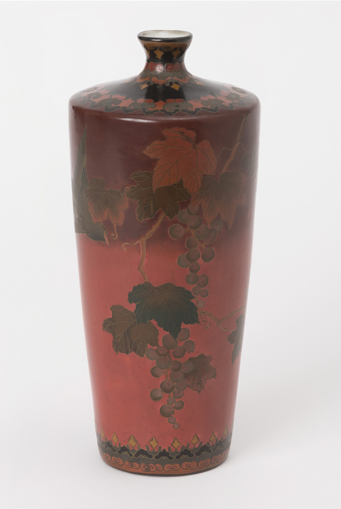 Housing recommended Cylindrical vase, tapered at bottom, angular shoulder tapering sharply to short narrow neck with outcurving lip. Shaded red ground with bird in flight, grapes, leaves and vine in muted greys, greens, browns. Border patterns around top and bottom in black, grey, yellow, red.