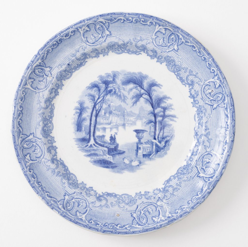 Plate with blue transfer print showing figures and swans in a fantasy landscape. Scrolling border with a striped ground.