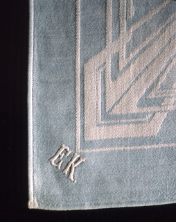 """Blue and white damask napkin with a geometric design incorporating circular and rectangular framing elements.  The monogram of Peter Behrens (PB) is woven into the center of the design. Initials """"E"""" """"K"""" embroidered in one corner. The four edges are machine hemmed."""