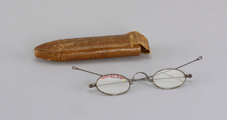 Steel-rimmed spectacles (a) in a case of cardboard covered with gold tooled leather