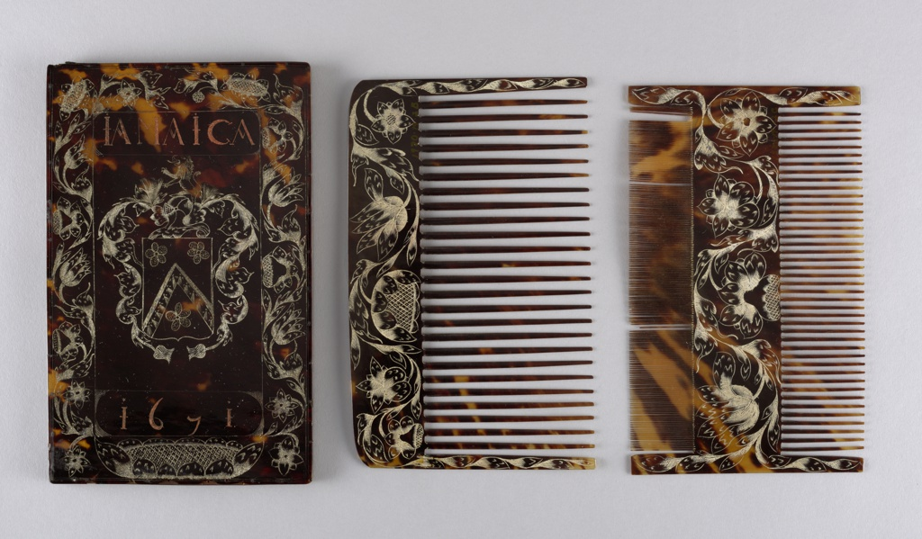 """Retangular case (a) with engraved decoration of floral borders surrounding a coat of arms with """"IAMAICA"""" etched above and """"1671"""" below; one large toothed comb (b) with engraved floral decoration along top and sides; double-sided comb (c), fine teeth one on side, large teeth on the other, engraved floral decoration on sides and center panel. Floral engraving and coat of arms picked out with white pigment; word and date with red-orange pigment."""
