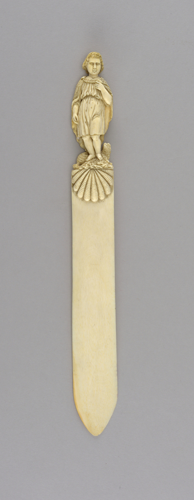 An ivory letter opener with a figure on the handle wearing a cape.