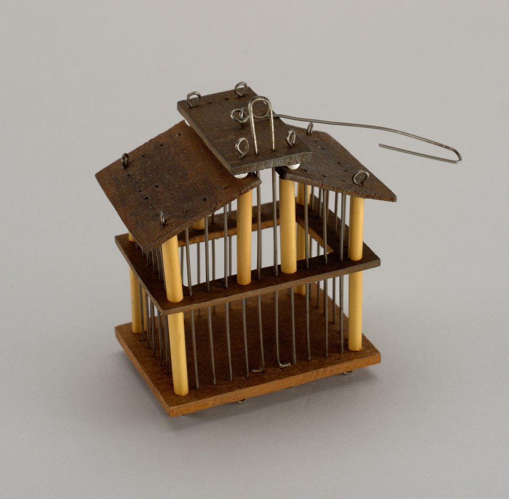 Rectangular form with gabled roof; corner posts sheathed in bamboo; looped wire for sliding door; wire hook in center of roof.