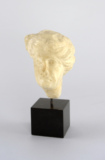 Fragment of a woman's head carved in marble, mounted on a wooden block.