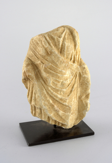 Fragment of a woman's torso with pleated robes. Head, hands and lower body missing.