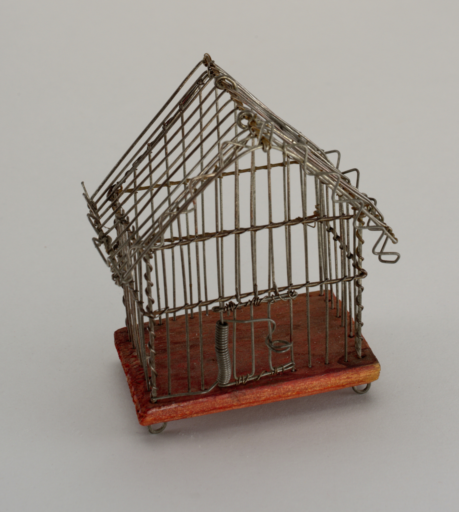 Upright rectangular cage with peaked roof having loop handle at top, zigzag wire along front and side edges; swinging door on spring; red-painted wood base with four circular wire feet.