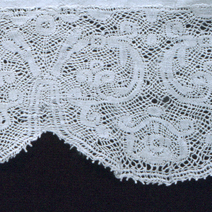 Bobbin lace band attached to narrow strip of linen. Pattern of symmetrical branching leaves with scalloped edge.