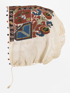 Woman's cap of white voile heavily embroidered in red, blue and yellow silks.