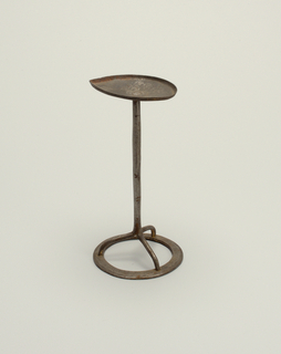 Old wrought steel oil lamp on tripod stand with ring foot a) single wick Betty lamp with cut-out bird on nail hinged cover. Handle bent forward, its hole holding a modern 8-shaped chain link, hooked into hanging staple. b) Tripod stand on ring base, with pointed oval tray on top.