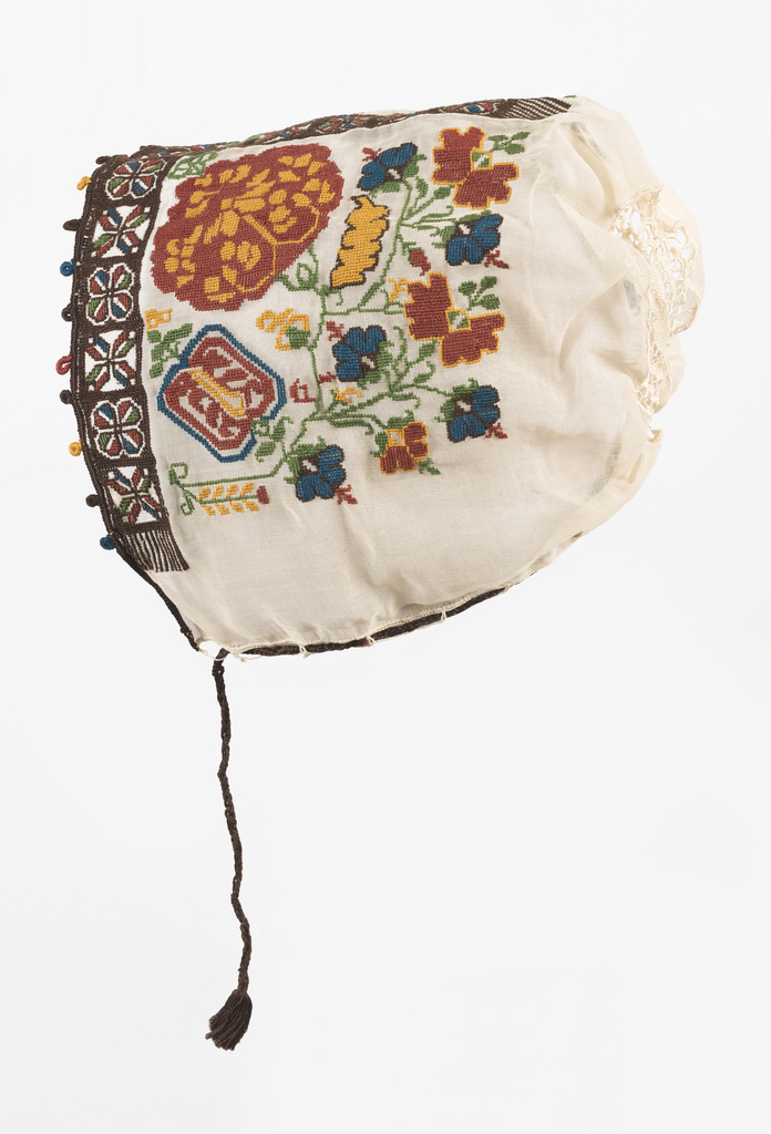 Woman's cap of fine white linen voile, embroidered in multi-colored silks. Narrow band on crown and bordering front in stylized design of open flower head. Sides embroidered in large stylized flower in red and yellow. At crown, a black oval of fine crocheted lace. Brown silk draw cord.