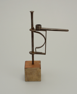Wood block base with wrought iron stem. Adjustable and articulated candle arm. No drip pan.