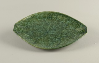 Oval form with two raised squared grips and a mottled green glaze.  Underdish for 1993-64-12.