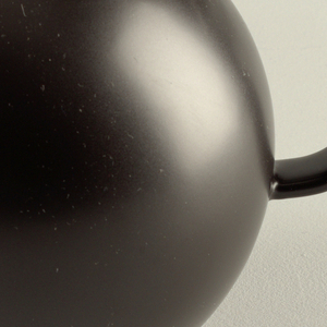 Round, globular form with a triangular spout and D-shaped handle that is squared off at the top.  Rounded lid with cylindrical finial with a rounded top. Decorated in a matte black finish.  Creamy stone color peeks out slightly from area where the lid meets the pot.