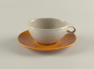 Gray cup with loop handle and tan saucer.